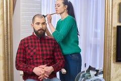 有胡子的人和化妆师 图库摄影