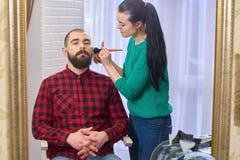 有胡子的人和化妆师 免版税库存图片