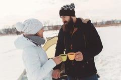 有胡子的人和女朋友喝咖啡在冬天高涨 免版税库存图片