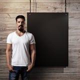 有胡子的人和黑横幅在木墙壁上 库存照片
