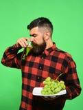 有胡子的人喝杯葡萄汁或酒 免版税库存图片