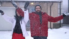 有胡子的人在培养手附近投掷极少数雪,妇女身分 愉快的夫妇获得一个乐趣在冬天后院 影视素材