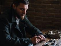 年轻有胡子的人在客栈喝威士忌酒,葡萄酒样式 免版税库存照片
