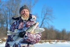 有胡子的人在成功的冬天渔以后拿着结冰的鱼冷的晴天 免版税库存图片