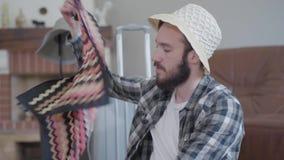 有胡子的人在房子佩带的帽子和围巾坐 近是移动的手提箱 股票录像