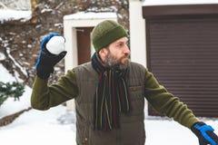 有胡子的人在手套在围场投掷雪球 库存图片