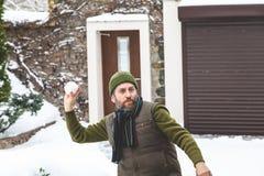 有胡子的人在手套在围场投掷雪球 免版税库存照片