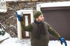有胡子的人在手套在围场投掷雪球 免版税图库摄影
