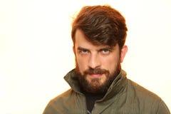 有胡子的人在有有趣的神色的卡其色的夹克穿戴了 关闭 E 空白 图库摄影
