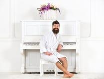 有胡子的人在浴巾享受早晨,当坐在钢琴附近时 快乐的人在钢琴音乐会前面坐 库存照片