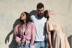 有胡子的人在热的晴天拥抱两个夫人 当人拥抱他们时,女孩转向了反面 三角爱 库存图片