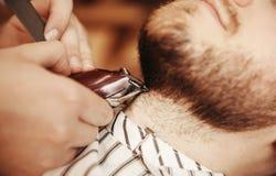 有胡子的人在理发店刮的剃刀美发师理发师 免版税库存图片