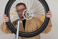有胡子的人在自行车上把前轮放 免版税库存图片