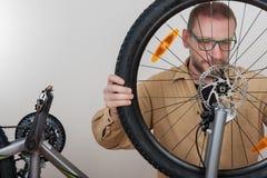 有胡子的人在自行车上把前轮放 图库摄影