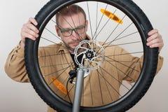 有胡子的人在自行车上把前轮放 库存图片