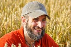 有胡子的人在麦田坐晴天 免版税库存图片