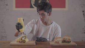 有胡子的人坐在开胃汉堡前面的桌上的和shawarma为吃做准备 人倾吐 股票录像