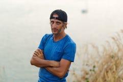 有胡子的人坐石栏杆在佩带在空白的蓝色T恤杉和黑盖帽的城市公园 库存照片