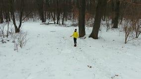 有胡子的人天线跳跃与跳绳的黄色外套的在冬天森林里 股票视频