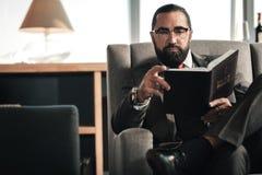 有胡子的人戴着眼镜和拿着圣经的手手表 免版税库存照片