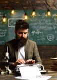 有胡子的人打字研究论文 在葡萄酒打字机的有胡子的人类型 在衣服工作的商人在书桌 免版税图库摄影