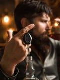 有胡子的人拿着玻璃白兰地酒 强壮男子喝 有汽车钥匙的确信的人在他的手上 不要喝并且不要驾驶 库存图片