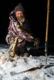 有胡子的人拿着鱼并且在黑暗的冬天晚上微笑着 图库摄影