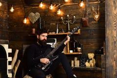 有胡子的人拿着黑电吉他 人有胡子的音乐家喜欢与低音吉他,木背景 人 库存图片