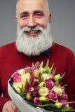 有胡子的人播种的射击有郁金香花束的  免版税图库摄影