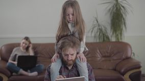 有胡子的人的画象与片剂关闭一起使用 一点哀伤的女孩坐父亲脖子 沙发的母亲 股票录像