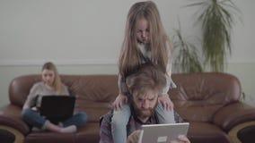 有胡子的人的画象与片剂关闭一起使用 一点哀伤的女孩坐父亲脖子 沙发的母亲 股票视频
