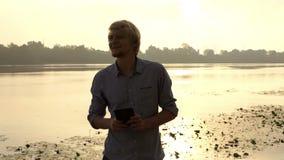 有胡子的人看他的智能手机并且对Dnipro微笑户外 股票录像
