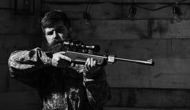有胡子的人穿伪装衣物,木内部背景 猎人,有以前瞄准的枪的残酷行家 免版税库存图片