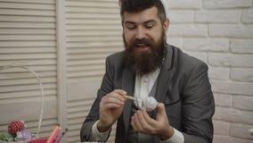 有胡子的人绘复活节彩蛋 Funy行家人佩带的兔宝宝耳朵为复活节做准备 复活节系列准备 股票录像