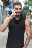 有胡子的人谈话与您在街道上的巧妙的电话 库存照片
