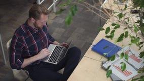 有胡子的人饮用的咖啡和浏览互联网,当放松在椅子时 影视素材