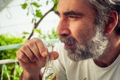 有胡子的人饮用的白兰地酒 免版税库存图片