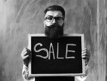 有胡子的人,在黑板的残酷白种人行家藏品销售题字 免版税库存照片