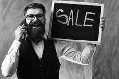 有胡子的人,有智能手机藏品销售题字的残酷白种人行家 免版税库存照片