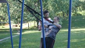 有胡子的健身教练员在夏天公园控制在健身圈的年轻人强烈的做的引体向上 4K缓慢的mo英尺长度 影视素材