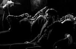 有胡子的典雅的年轻人坐在葡萄酒roo的一个沙发 图库摄影