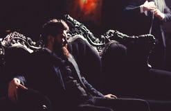 有胡子的典雅的年轻人坐在葡萄酒roo的一个沙发 免版税库存图片