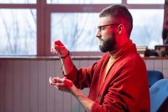有胡子的占卜者戴着眼镜和镯子读书oracle卡片 免版税库存图片