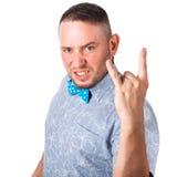 有胡子的可爱的成人人在显示姿态的夏天衬衣的一个蓝色蝶形领结 免版税库存照片