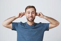 有胡子的可爱的白种人男性花费业余时间快乐,捏耳朵作为与孩子的戏剧,有好心情,棍子 图库摄影