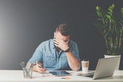 年轻有胡子的哀伤的商人在他的手上坐在桌上,盖他的面孔用他的手和拿着智能手机 免版税库存照片