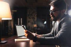 有胡子的商人佩带的眼睛玻璃和使用赞成计算机在现代办公室在晚上 工友举行智能手机 免版税库存图片