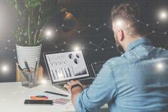 年轻有胡子的商人在办公室坐在桌上和使用有图、图表和图的膝上型计算机在屏幕上 库存照片