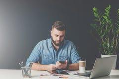 年轻有胡子的商人在办公室坐在桌上并且使用智能手机 免版税库存图片