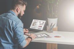 年轻有胡子的商人在办公室坐在桌上,使用片剂计算机并且探索图,做笔记 免版税库存照片